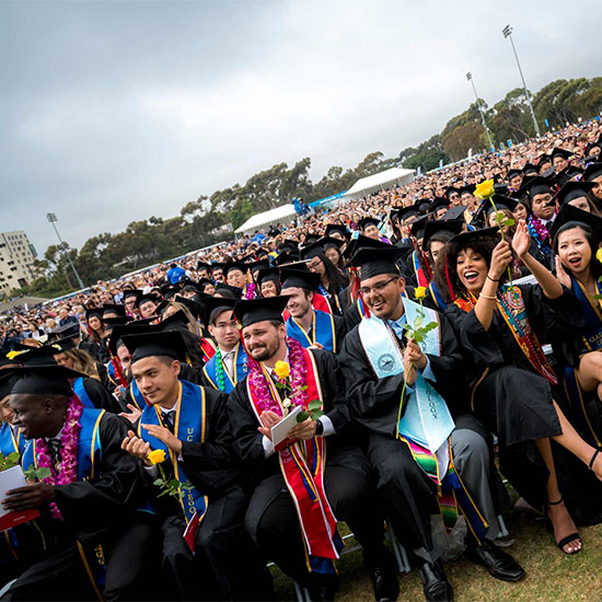 UC San Diego students at commencement - wearing caps and gowns and celebrating while sitting in the first row of a crowd of attendees
